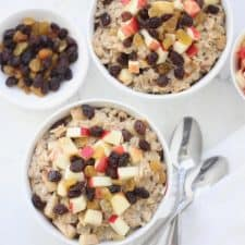 Apple raisin oatmeal in white bowl with two spoons.