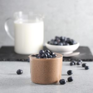 Chocolate pudding in glass on grey surface with blueberries.