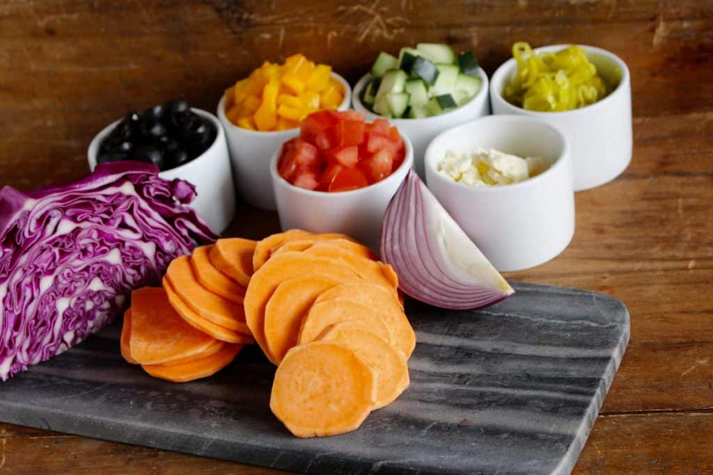 Vegetables in white bowls on a grey cutting board.