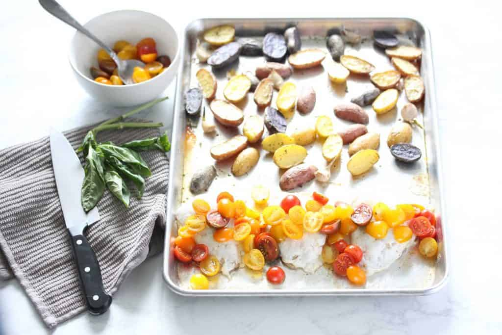 Chicken, tomatoes and baby potatoes on sheet pan.