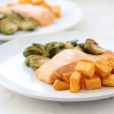 Salmon, sweet potatoes and Brussels sprouts on white plate.