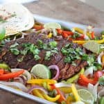 Flank steak, peppers and onions on sheet pan.