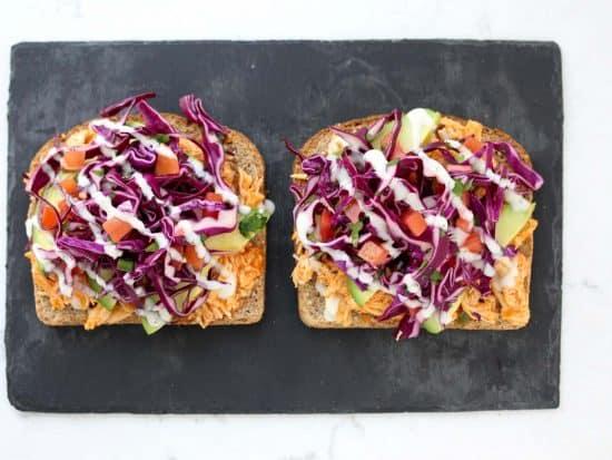 Open face buffalo chicken sandwich on grey stone cutting board.