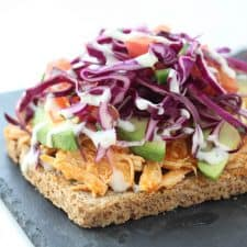 Open face buffalo chicken sandwich on grey stone cutting board.