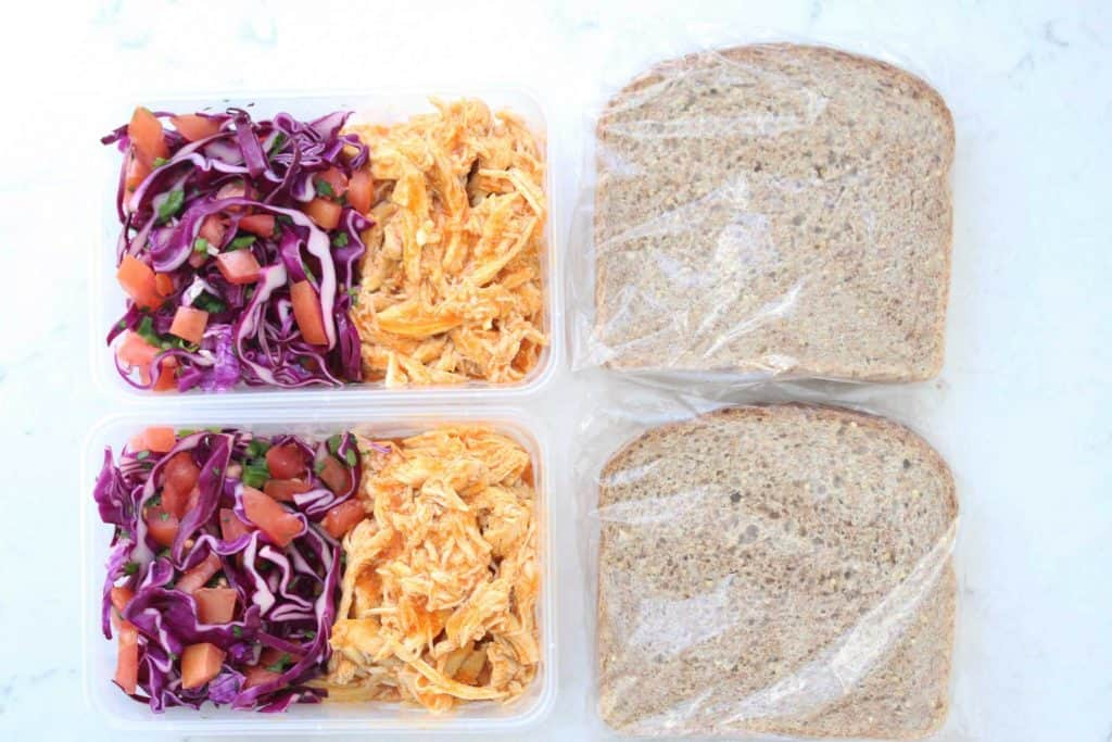 Vegetables and chicken in plastic containers next to slices of bread.