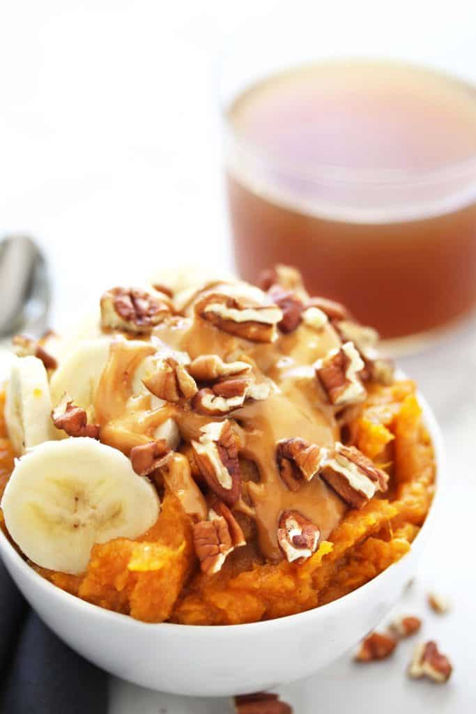 Sweet potatoes with banana slices, peanut butter and walnuts in a white bowl on grey napkin.