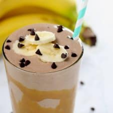 Chocolate smoothie with banana slices in clear glass on white surface.
