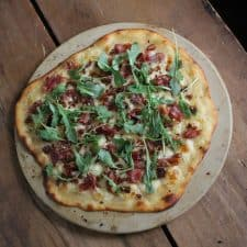 Flatbread on pizza stone on wood surface.