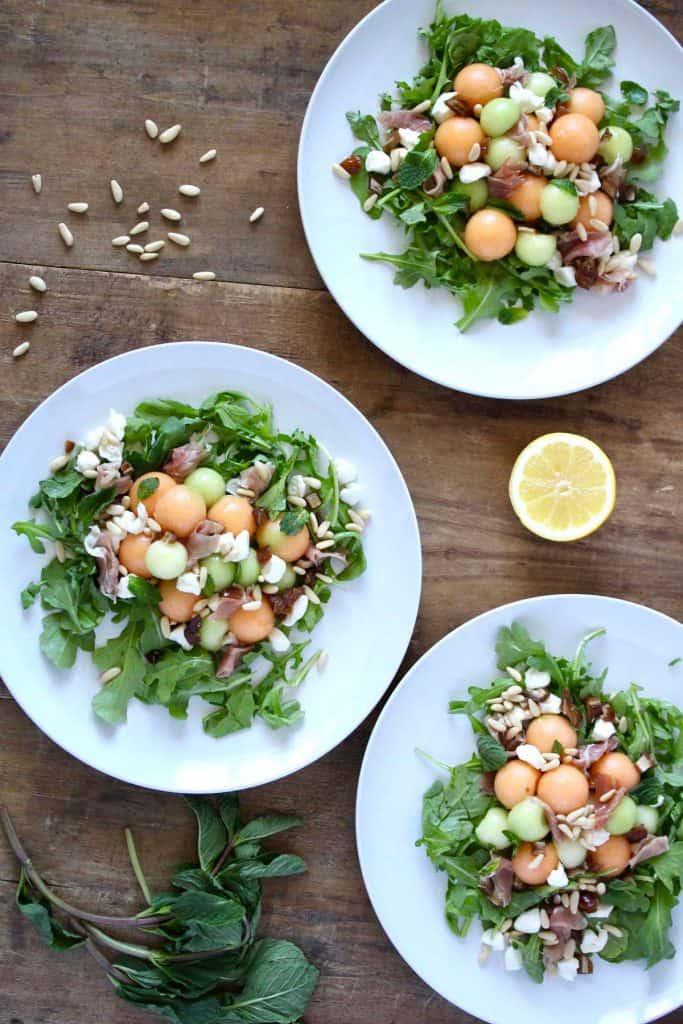 Salad on three white plates on wood surface.