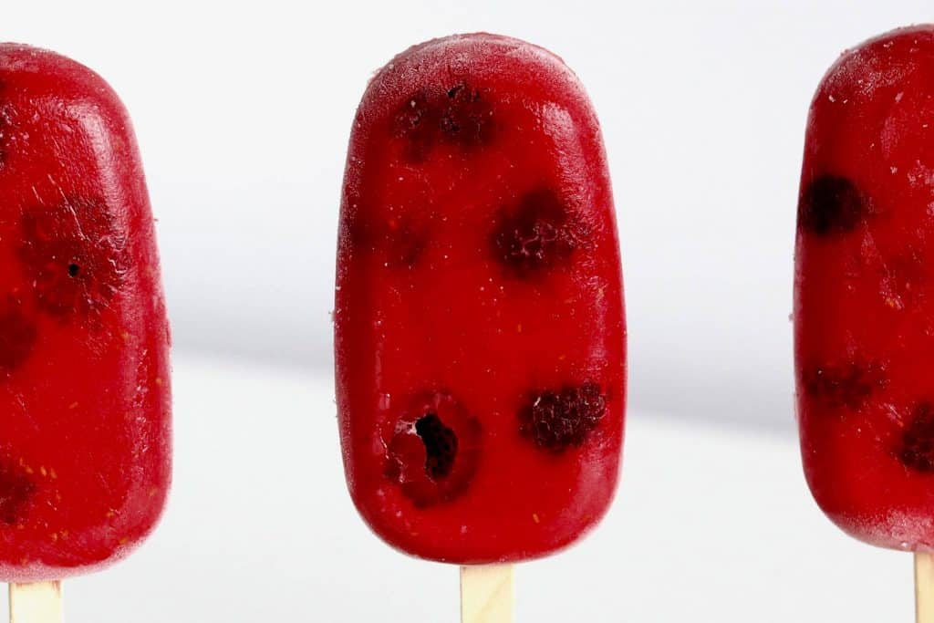 Red popsicle on white background.