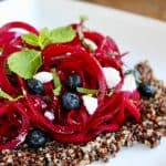 Beet noodles with blueberries and goat cheese on white plate.