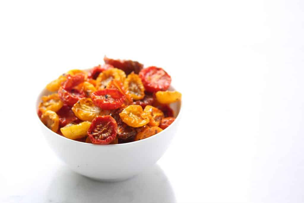 Slow roasted cherry tomatoes in white bowl.