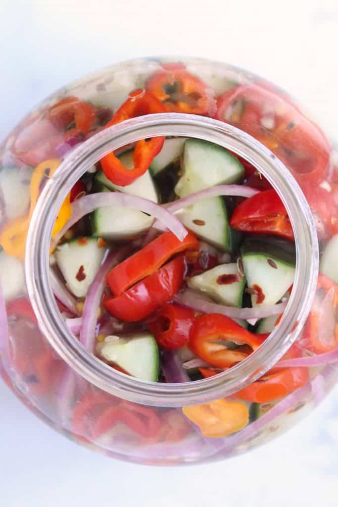 Pickles and peppers in clear mason jar on white surface.