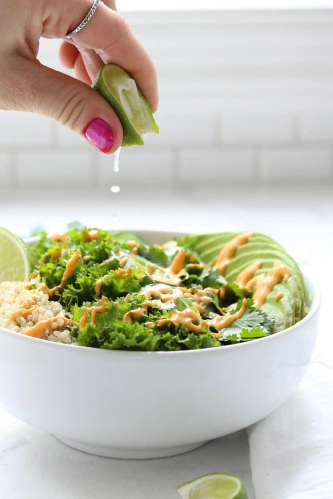 Hand squeezing lime over green grain bowl.