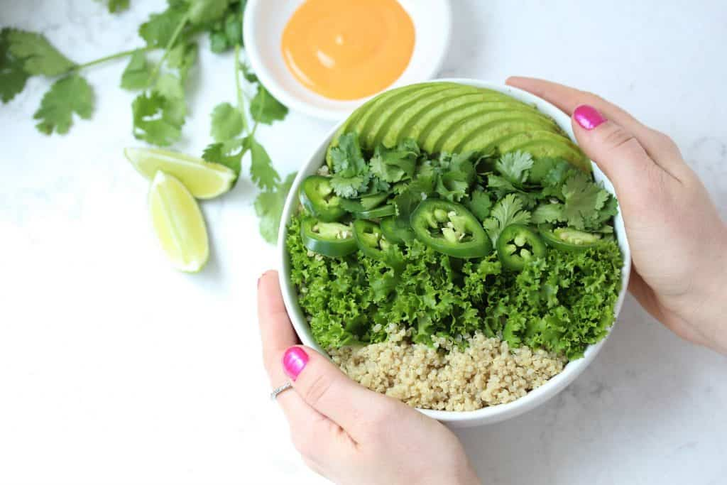 Two hands holding white bowl of greens and quinoa.