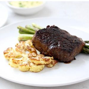 Steak, cauliflower and asparagus on a white plate with hollandaise.