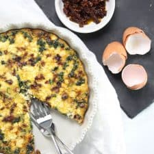 Quiche in white dish with two forks.