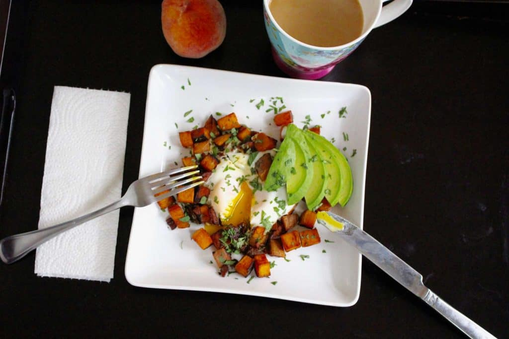 Sweet potatoes, avocado and runny egg on white plate.
