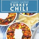 Chili in white bowls on blue plaid napkins.